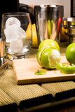 Cocktail preparation: glasses, shaker and fruits on a wooden board Royalty Free Stock Image