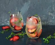 Cocktail of Prosecco. A cocktail of Prosecco with plums and thyme Stock Photos