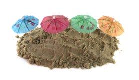 Cocktail-Regenschirm im Sand-Hügel Stockfotografie
