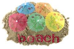 Cocktail-Regenschirm im Sand-Hügel Stockfoto