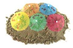 Cocktail-Regenschirm im Sand-Hügel Stockbild