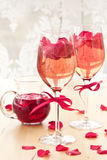 Cocktail with rose petals. Pink Cocktail with fresh rose petals on wooden table royalty free stock photography