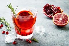Cocktail rosso con l'arancia sanguinella ed il melograno Bevanda di rinfresco di estate Aperitivo di festa per la festa di Natale immagine stock