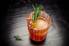 Cocktail rosso dell'alcool con i rosmarini, la scorza d'arancia e il iceball Fotografie Stock