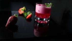 Cocktail rosso fresco con i cubetti di ghiaccio e le foglie di menta Bacche rosse di estate video d archivio
