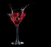 Cocktail rouge éclaboussant dans le verre sur le noir Photo stock