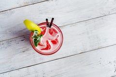 Cocktail rouge avec de la glace et la chaux sur le fond en bois blanc Images stock