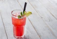 Cocktail rouge avec de la glace et la chaux sur le fond en bois blanc Images libres de droits