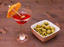 Cocktail rouge avec le parapluie et les olives sur le bois Images libres de droits