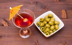 Cocktail rouge avec le parapluie et les olives sur le bois d'en haut Photographie stock libre de droits