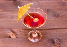 Cocktail rouge avec le parapluie sur le bois d'en haut Photographie stock
