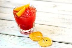 Cocktail rouge d'alcool avec les tranches et la glace oranges photographie stock