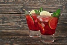 Cocktail rouge de deux plans rapprochés avec la menthe, la chaux et la glace Images libres de droits