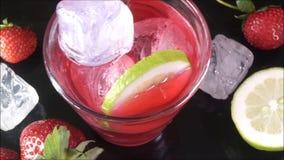 Cocktail rouge de nrgroni avec la tranche jaune de glaçons blancs de citron banque de vidéos
