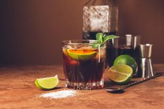 Cocktail of rum and cola ice cubes and lime in a glass goblet on a dark brown background. Strong alcoholic drink. royalty free stock image
