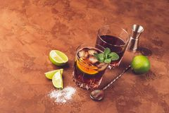 A cocktail of rum ice cubes and juicy lime in glass goblets against a dark brown background. Strong alcoholic drink. stock photo