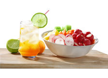 Cocktail and Salad Fruit. Cocktail glass decorated with a lime slice and a bowl of salad fruit isolated on white background Royalty Free Stock Photo
