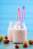Cocktail saudável do leite com as morangos frescas em uns frascos de pedreiro em b Foto de Stock