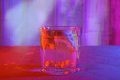 Cocktail with sea buckthorn, mint, lemon on the table, anaglyph and glitch effect, neon light royalty free stock photography