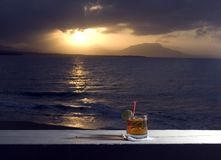 Cocktail by the sea rum on rocks. Rum on rocks Cocktail by the sea at sunset with island in distance Dominican Republic Caribbean Stock Image