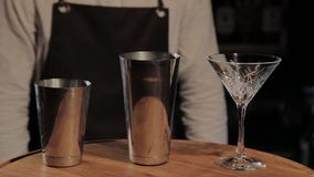 Cocktail shaker and beaker for preparation beverages on bar counter in pub close up. Cocktail bar utensils, shaker and