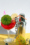 Cocktail shaker & cocktail. Stainless steel cocktail shaker,red cocktail with slice lemon and green umbrella Royalty Free Stock Photography