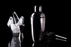 Cocktail shaker, swizzle, tongs and spoon with ice in a bucket for preparing a summer cocktail beverage on a black table. With copy space with copy space Royalty Free Stock Photography