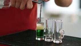 Cocktail shot green mexican with banana liqueur, lemon juice and tequila -beverage on a bar counter . Service barman concept stock video