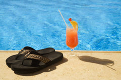 Cocktail and slippers stand on edge of pool. Royalty Free Stock Photo