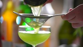 Cocktail slowly pours through sieve. Male hand holds a sieve. Fresh juice for delicious beverage. Fresh taste of kiwi daiquiri stock footage