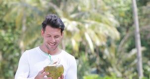 Cocktail sobre palmeiras, Guy Tourist novo de sorriso feliz do coco da bebida do homem vídeos de arquivo