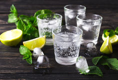Cocktail with soda water, ice, lime and mint. Summer cocktail with soda water, ice, lime and mint on black wooden table. Selective focus Stock Image