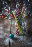 Cocktail a spirale multicolori della paglia in un muratore di vetro del barattolo su un fondo festivo del ` s del nuovo anno Tabe Immagine Stock