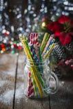 Cocktail a spirale multicolori della paglia in un muratore di vetro del barattolo su un fondo festivo del ` s del nuovo anno Tabe Immagini Stock