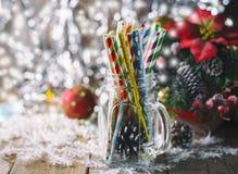 Cocktail a spirale multicolori della paglia in un muratore di vetro del barattolo su un fondo festivo del ` s del nuovo anno Tabe Immagini Stock Libere da Diritti