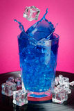 Cocktail splash. A blue cocktail with ice cubes making a splash stock photo