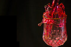 Cocktail Splash. A red colored cocktail being poured in a glass in a party, on a black background Royalty Free Stock Images