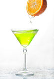 Cocktail splash in glass  with an orange on a white Royalty Free Stock Photo