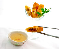 Cocktail springroll with sweet plum sauce. Cocktail springroll with one taken by chopsticks Stock Images