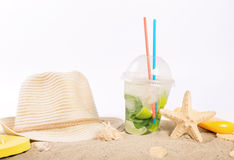 Cocktail, straw hat, beach slippers, lotion, starfish on the san Stock Images