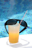 Cocktail and sunglasses. At the edge of pool Royalty Free Stock Photo