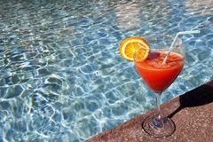 Cocktail at swimming pool. Cocktail with a slice of orange at swimming pool Stock Photography