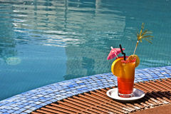 Cocktail at swimming-pool. A colorful cocktail near swimming-pool Stock Photography