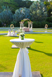 Cocktail table and with wedding arch background. Cocktail table and wedding arch in a outdoor garden setting Stock Image