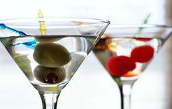Cocktail time !. Two martinis with colorful swizzle sticks garnished one with olives and the other with cherries Royalty Free Stock Photos