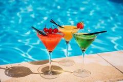 Cocktail tropicale variopinto con le bacche sul bordo della piscina fotografia stock
