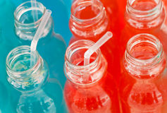 Cocktail tubes in jugs with colorful energy drings with syrup, red and blue colors. Stock Image