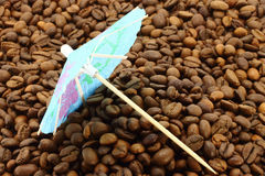 Cocktail umbrella on a coffee beans Royalty Free Stock Photo
