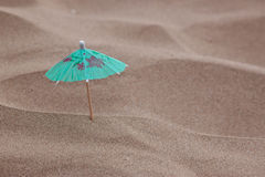 Cocktail umbrella in sand Stock Photos