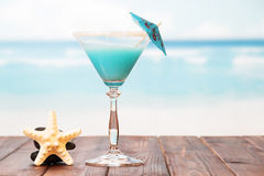 Cocktail with umbrella and starfish on  sea background. Stock Images
